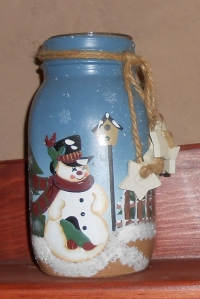 A regular mouth quart jar that is painted and has a glass votive candle holder inserted into its top. Add decorations around jar neck.